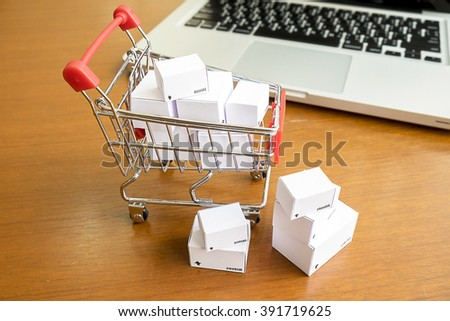 Shopping cart with boxes on  desk table with computer.Internet online shopping concept.Vintage tone retro filter effect,soft focus(selective focus) - stock photo