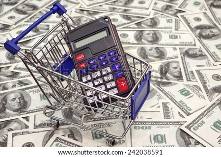 Shopping Cart with Calculator with empty display and  US Dollars Bills in the Background - stock photo