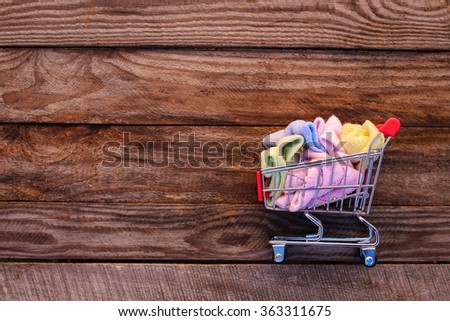 Shopping cart with clothing on the old wood background. Toned image. - stock photo