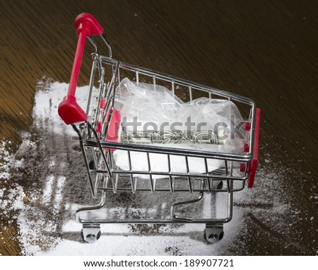 Shopping cart with cocaine and dollar inside - stock photo