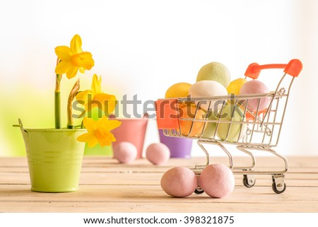 Shopping cart with colorful easter eggs and daffodils in a flowerpot - stock photo