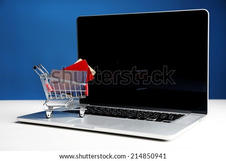 Shopping cart with credit cards on laptop on table, on blue background