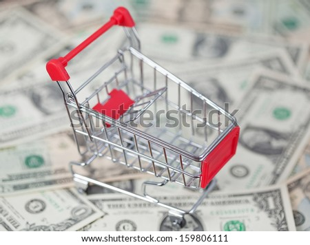 Shopping cart with dollars as a background - stock photo
