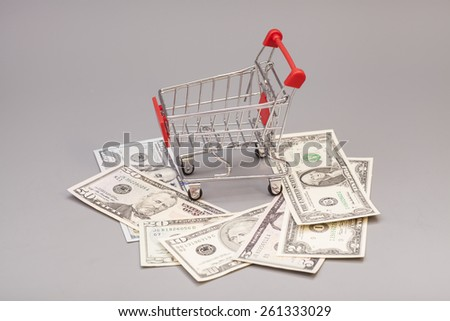 Shopping Cart with dollars isolated on gray - stock photo