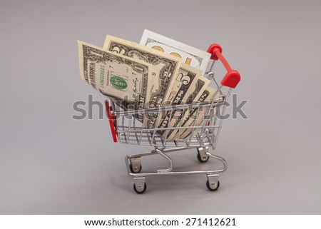 Shopping Cart with dollars isolated on gray