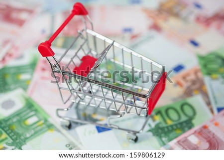 Shopping cart with euros as a background - stock photo