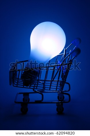 Shopping cart with light bulb in dark blue light. - stock photo