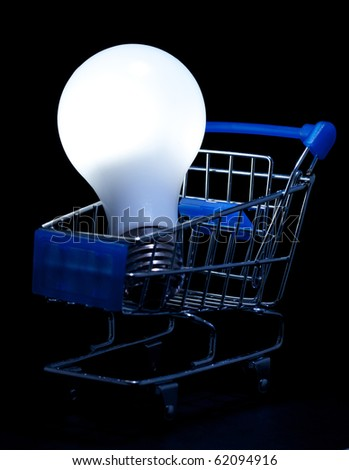 Shopping cart with lightning light bulb on black background. - stock photo