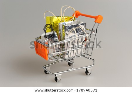 Shopping cart with packages on gray background