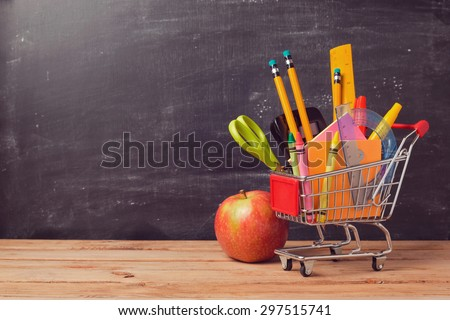 Shopping cart with school supplies over chalkboard background - stock photo