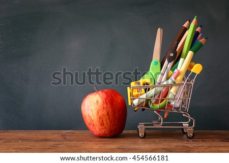 Shopping cart with school supply and apple in front of blackboard. Back to school concept  Back to school concept with - stock photo