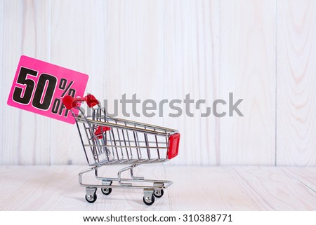 Shopping cart with tag of discount or sale,on the wooden background with copy space  - stock photo
