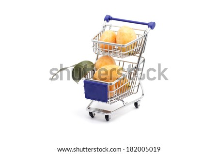 Shopping cart with tropical fruit isolated on white