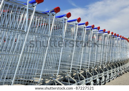 Shopping carts in a row against blue sky