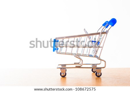 shopping carts on the wooden floor. isolated on white - stock photo