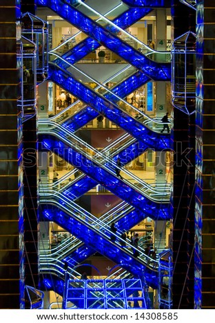 Shopping center interior. Crossed escalators with some people, lifts, floors. - stock photo