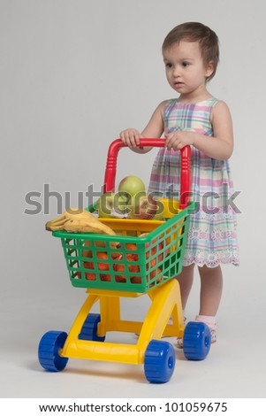 Shopping concept - child with shopping cart full with groceries - stock photo