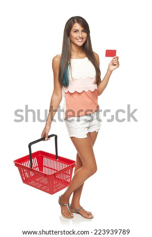 Shopping concept. Happy full length woman standing with empty red shopping basket and showing blank credit card, white background - stock photo