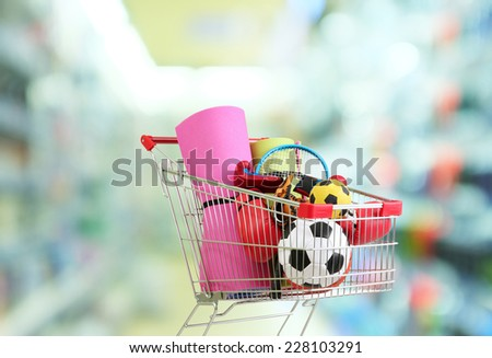 Shopping concept. Shopping cart with sport equipment on shop background - stock photo