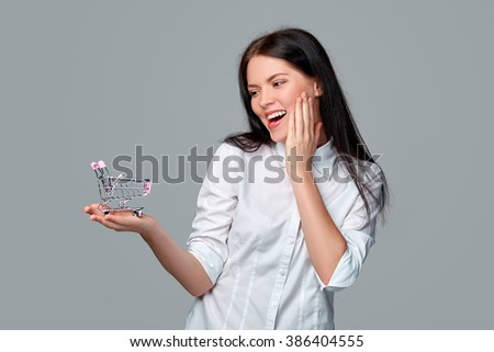 Shopping concept. Smiling happy young woman showing small empty supermarket shopping cart on her palm and showing OK sign, on grey background.