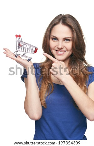 Shopping concept. Smiling young woman holding small empty supermarket shopping cart on her palm and pointing at it, over white background - stock photo