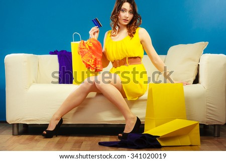 Shopping consumerism concept. Young woman with credit card buying sitting on sofa with paper bags and new clothes - stock photo