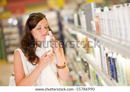 Shopping cosmetics - woman smelling bottle of shampoo in supermarket - stock photo