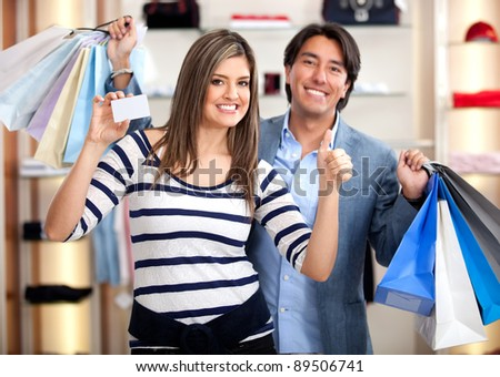 Shopping couple paying by credit card at a retail store - stock photo