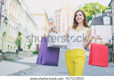 Shopping day. Attractive young woman with paper bags walking on city street. - stock photo