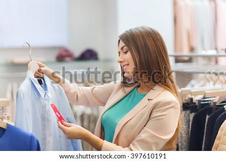 shopping, fashion, clothes, style and people concept - happy young woman looking at shirt price tag label in mall or clothing store