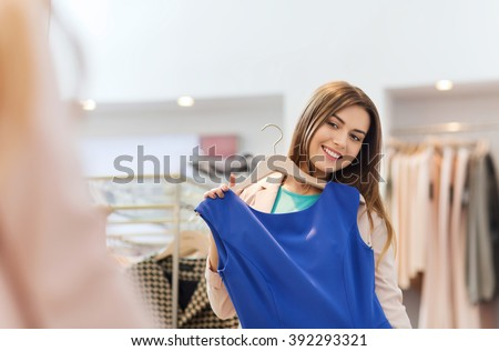shopping, fashion, style and people concept - happy woman choosing clothes and looking to mirror in mall or clothing store - stock photo