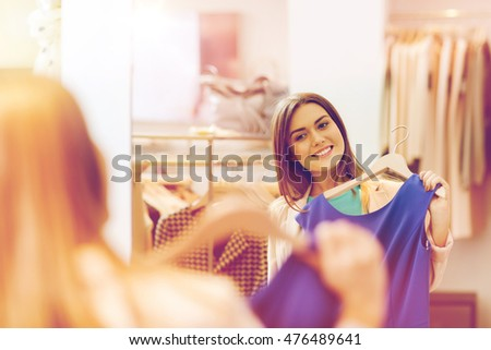 shopping, fashion, style and people concept - happy woman choosing clothes and looking to mirror in mall or clothing store