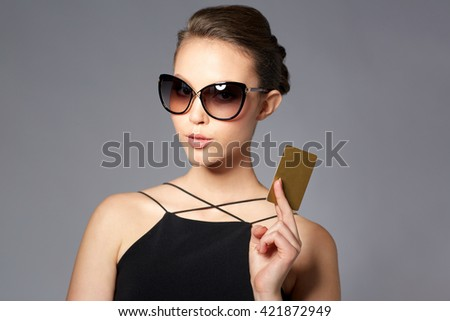 shopping, finances, fashion, people and luxury concept - beautiful young woman in elegant black sunglasses with credit card over gray background - stock photo