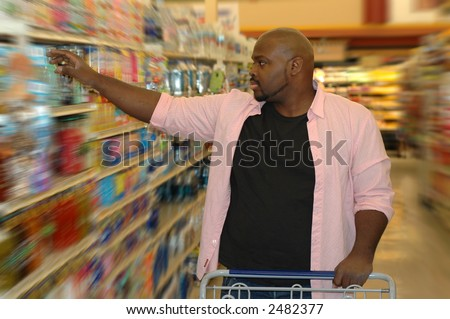 Shopping for groceries.  Picking an item off the shelf. - stock photo