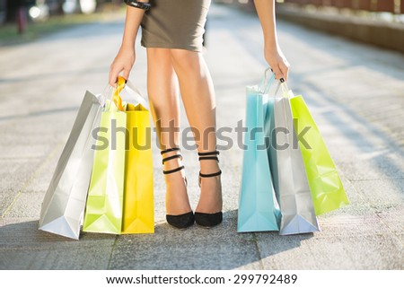 Shopping for new summer clothes. Close up of a female legs. Woman carrying lots of colorful shopping bags. She is wearing pencil skirt and trendy high heel shoes. - stock photo