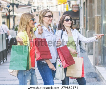 Shopping Girlfriends looking at shop window on the street. - stock photo