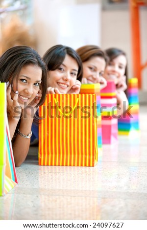 shopping girls on the floor in a mall with some bags - stock photo
