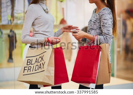 Shopping girls with paperbags talking in the mall - stock photo