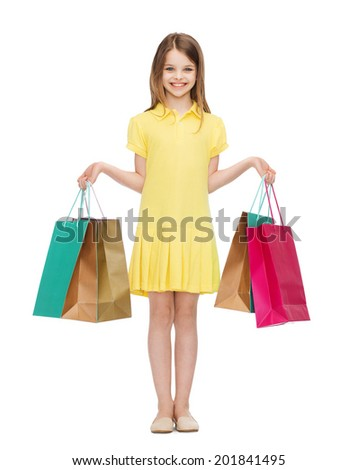 shopping, happiness and people concept - smiling little girl in yellow dress with shopping bags - stock photo