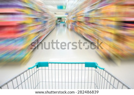 Shopping in supermarket shopping cart view with motion blur - stock photo