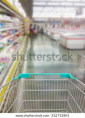 Shopping in supermarket with shopping cart - stock photo