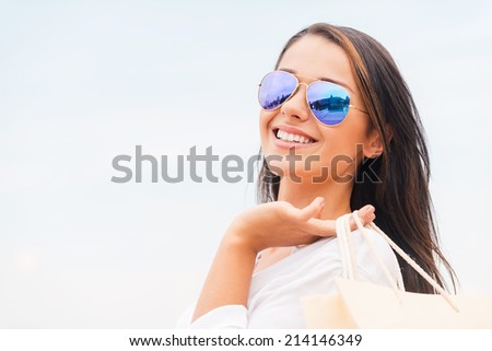 Shopping is my life! Rear view of beautiful young woman holding shopping bags and looking over shoulder with smile while standing outdoors - stock photo