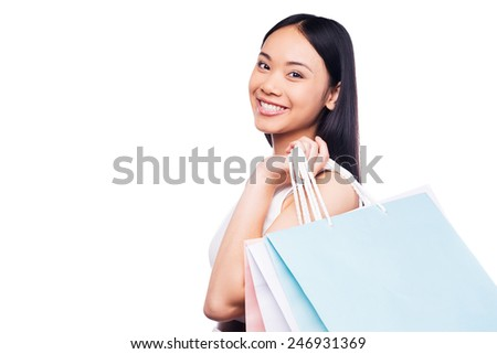 Shopping is the best female occupation! Side view of beautiful young Asian woman in pretty dress looking at camera and holding shopping bags while standing against white background   - stock photo