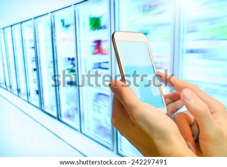 Shopping list on her smartphone at supermarket. - stock photo