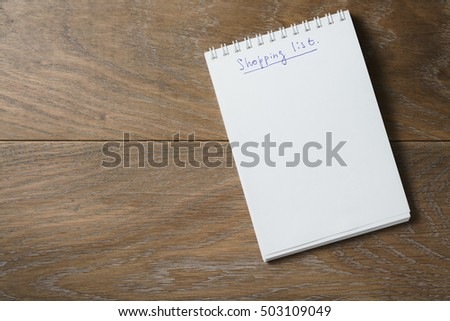 shopping list on notepad on wood table blank notepad for your text