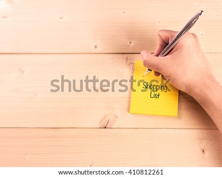 Shopping list on sticky note with man hand writing on wood - stock photo