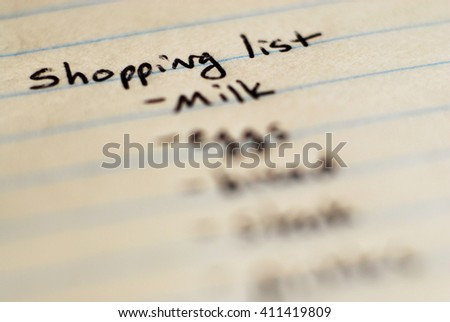 Shopping list written on paper for buying groceries on budget - stock photo
