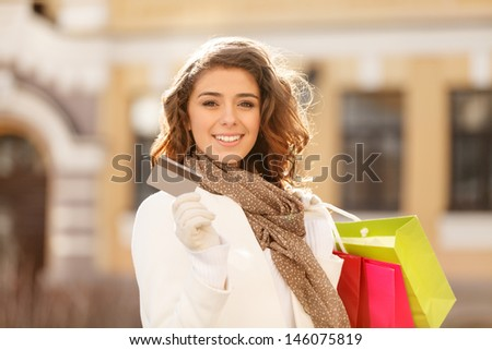 Shopping made easy! Beautiful young women holding a credit card in one hand and the shopping bags In another one - stock photo