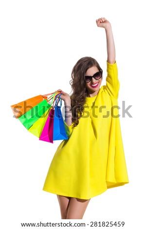 Shopping Makes Me Happy. Smiling elegance young woman in yellow mini dress holding colorful shopping bags and rising arm. Three quarter length studio shot isolated on white. - stock photo