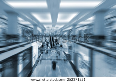 Shopping mall with unrecognizable people moving on escalators with motion blur in Dubai, UAE. Radial zoom defocused editing, blue tone image. Social gathering and globalization concept. - stock photo